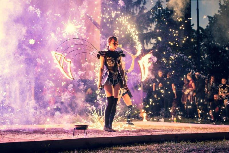 Flickan är en aktör av en etappshow bland gnistorna royaltyfri foto