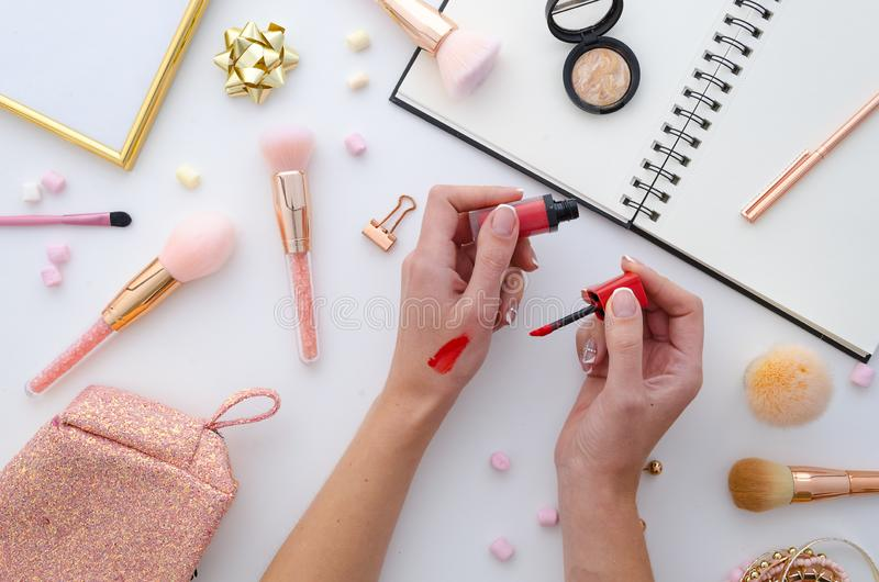 Flickan är hållande läppstift i händer, makeupprovkartor, anteckningsbok highlighter sminkskönhetsmedel på vit bakgrund Lekmanna- arkivfoton