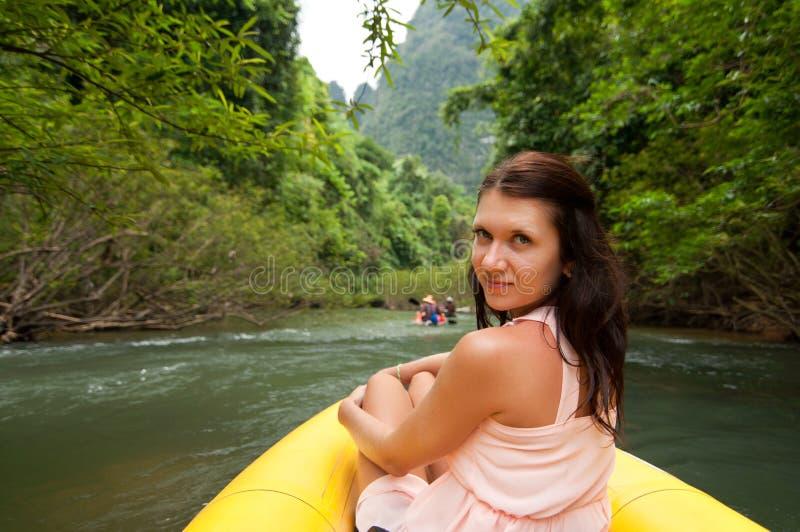 Flickan är i kanoten på bergfloden arkivfoton