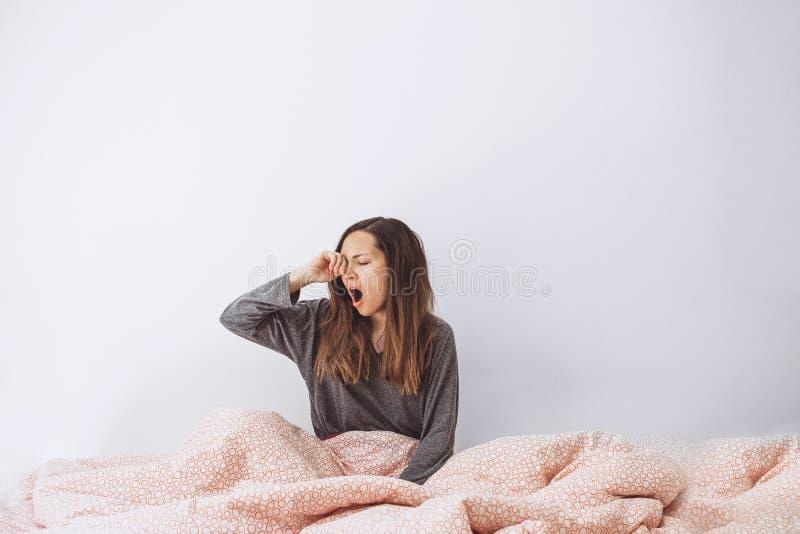Flickan är i säng och gäspningar royaltyfri fotografi