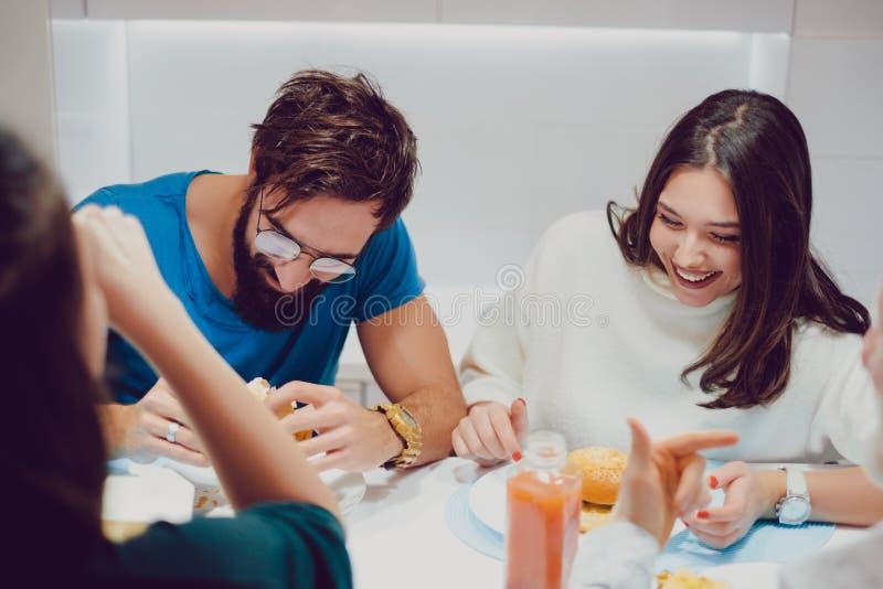 Flickan är laughnig medan på lunchen med vänner royaltyfri bild