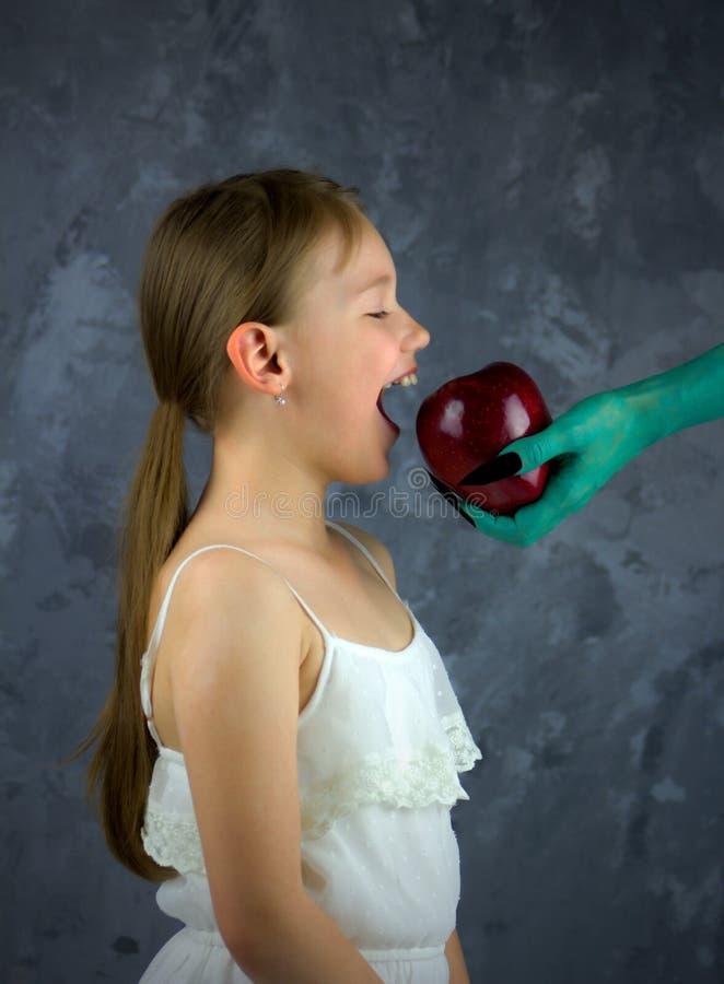 Flickan är omkring till tuggor som äpplet erbjöd vid häxan Snövitsagan arkivfoto