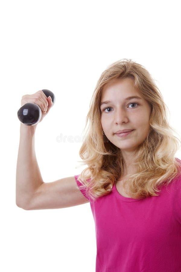 Flickan är sportslig med hantlar arkivfoto