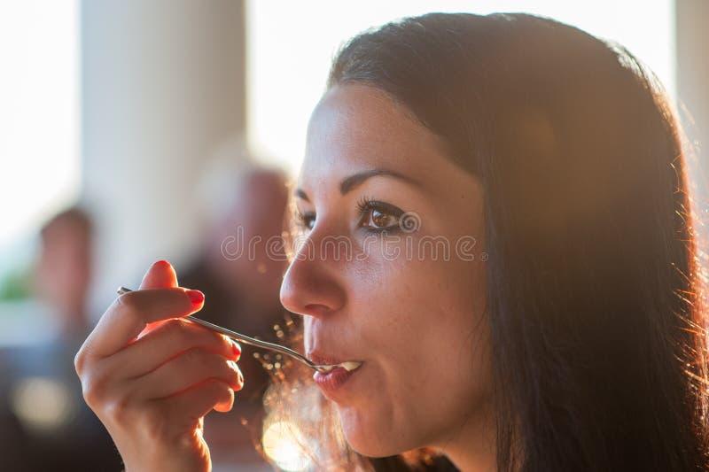Flickan äter en skednärbild En kvinna tycker om ett läckert mål som är fullt av mun Solstr?lar läcker mat i kafét solnedgångmat royaltyfri foto