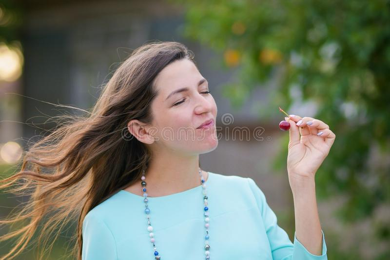 Flickan äter körsbär gå ner gatan, rymmer livliga sinnesrörelser, attraktiva kala skuldror för den unga kvinnan den körsbärsröda  royaltyfri bild