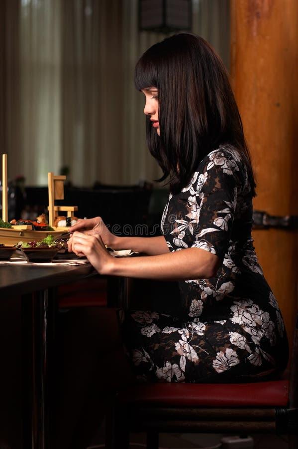 Flickan äter sushi 2 royaltyfri bild
