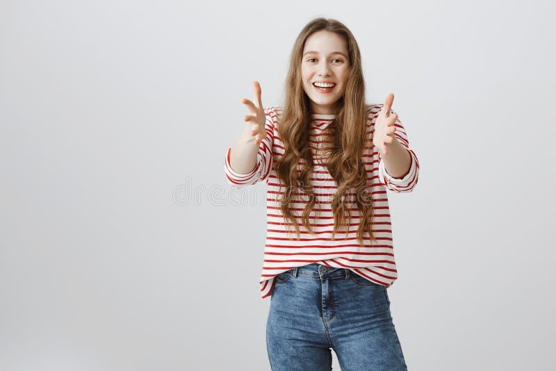 Flickan önskar åtstramningen dig tätt i omfamning Stående av den positiva snygga unga kvinnlign som drar armar in mot kamera royaltyfri fotografi