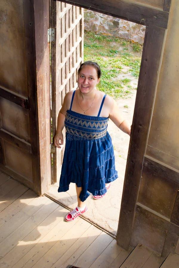 Flickan öppnar dörren royaltyfri fotografi