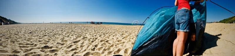 Flickan öppnar ett tält på stranden royaltyfri bild