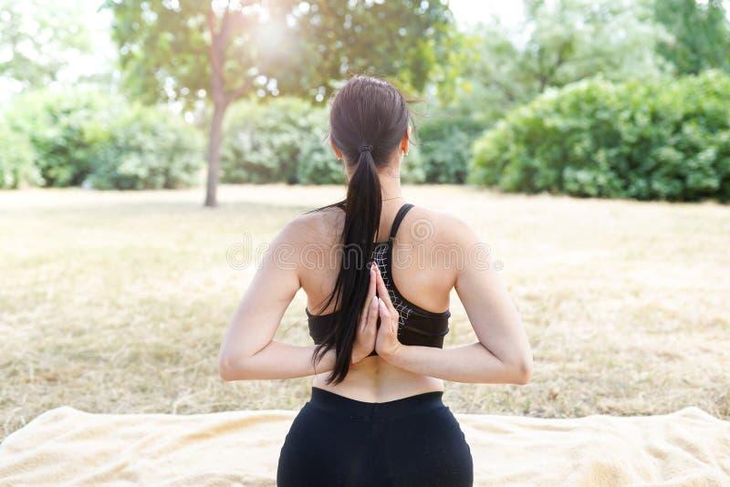 Flickan öva yoga och mediterar, naturbakgrund med kopieringsutrymme arkivfoto