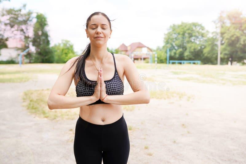 Flickan öva yoga och mediterar, naturbakgrund med kopieringsutrymme, sund livsstil royaltyfri bild