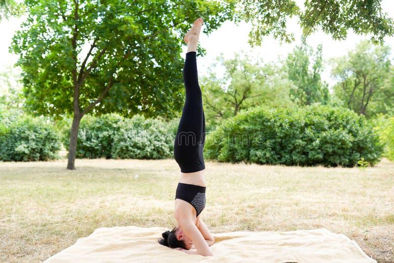 Flickan öva yoga och mediterar, naturbakgrund med kopieringsutrymme, sund livsstil royaltyfri fotografi