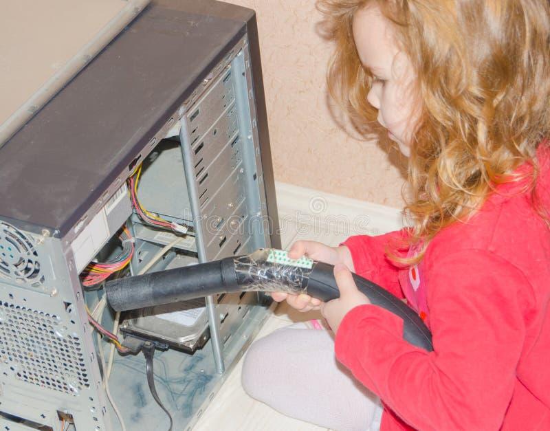 Flickan absorberar hemdatordammsugare arkivbild