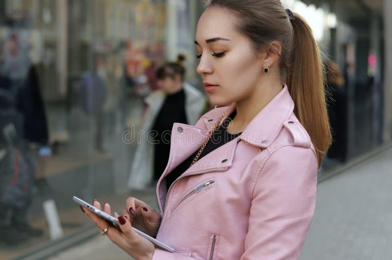 Flickan använder applikationerna på minnestavlan arkivfoto