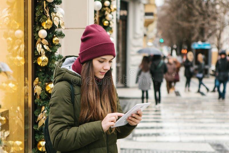 Flickan använder en minnestavla på en stadsgata under julferierna royaltyfri fotografi