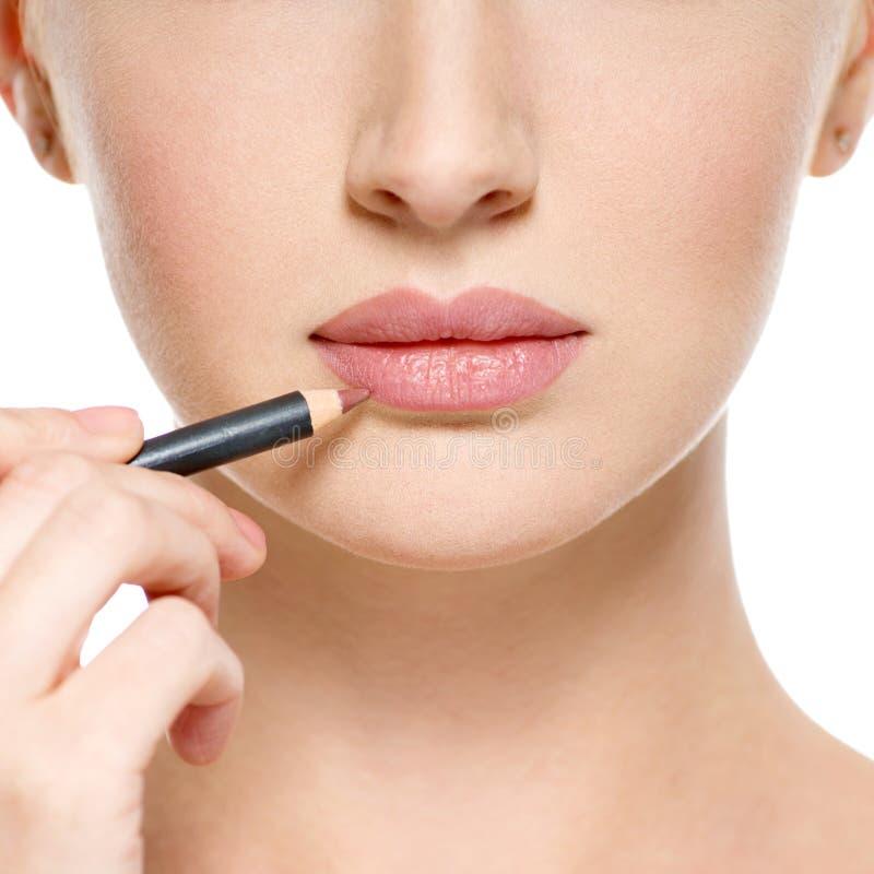 Flickan applicerar läppstift med den kosmetiska blyertspennan på kanterna arkivbilder