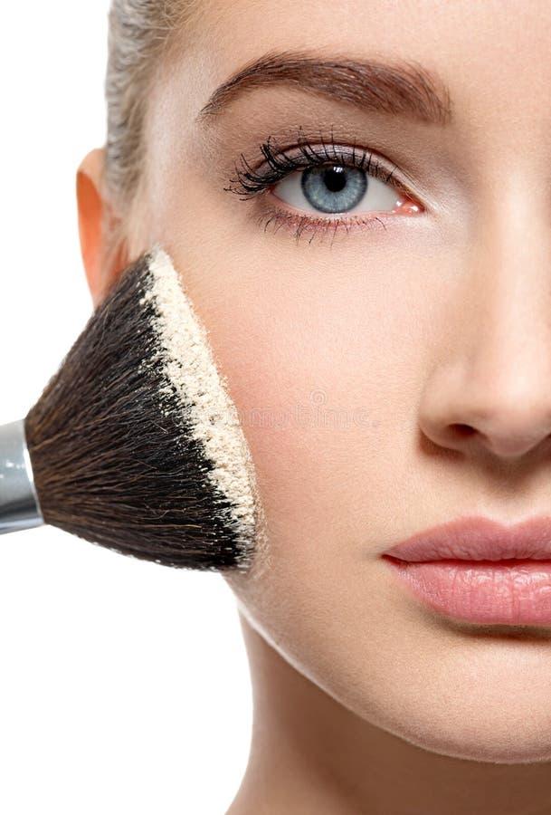 Flickan applicerar pulver på framsidan genom att använda makeupborsten arkivbild
