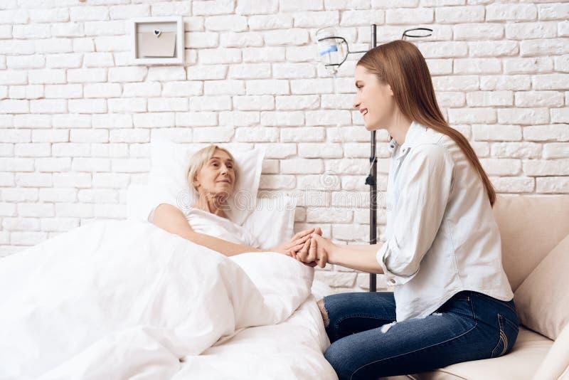 Flickan att bry sig för äldre kvinna hemma De rymmer händer royaltyfria foton