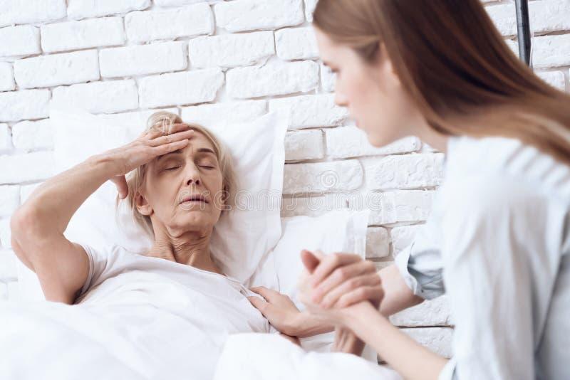 Flickan att bry sig för äldre kvinna hemma De rymmer händer Kvinnan känner sig dålig royaltyfria bilder