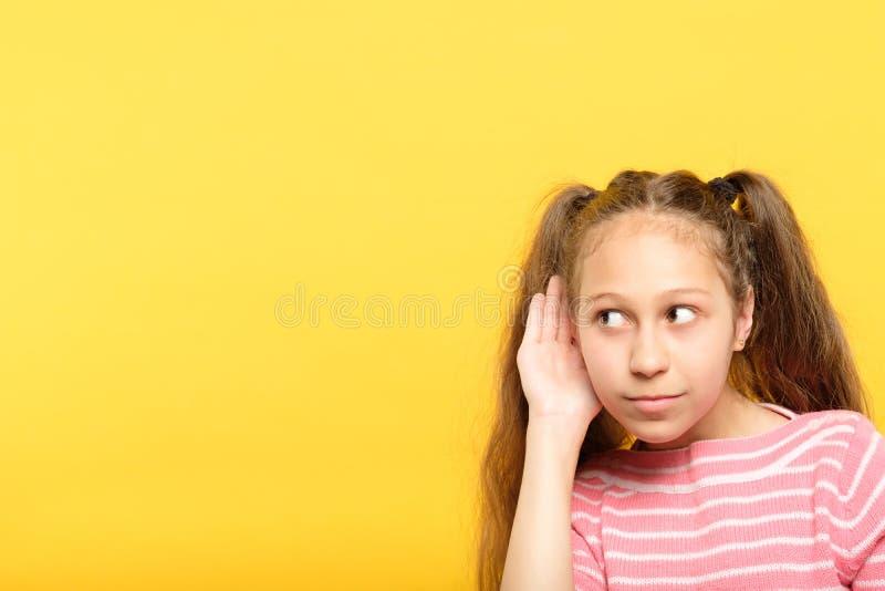 Flickan att tjuvlyssna för att lyssna hemligheter skvallrar kuriositet bänder upp royaltyfri fotografi