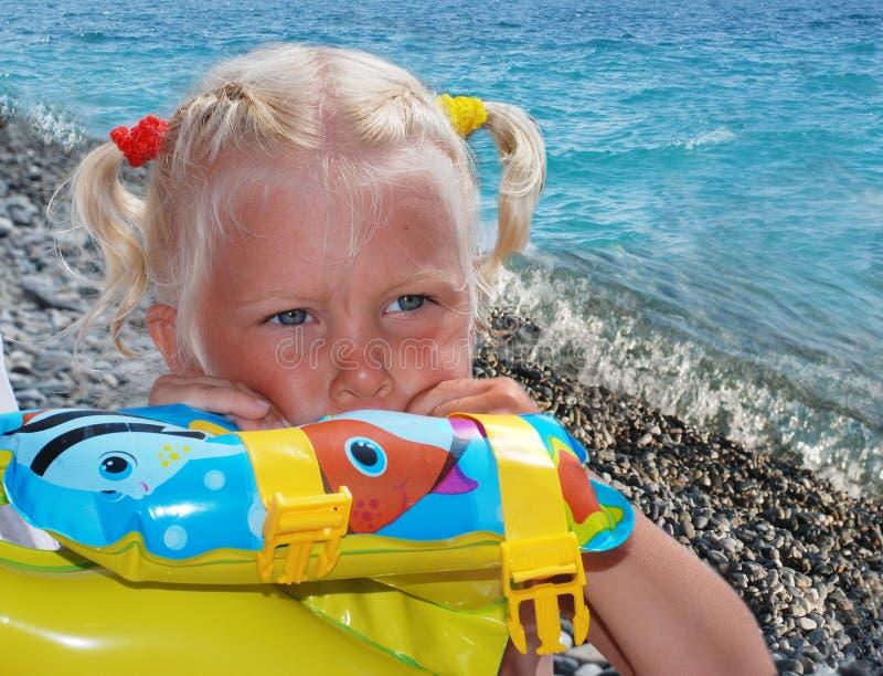 Flickan av 3 år, blondinen, på en havsstrand fotografering för bildbyråer