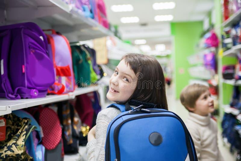 Flickan av 8 år shoppar in välja portföljen för skola royaltyfri bild