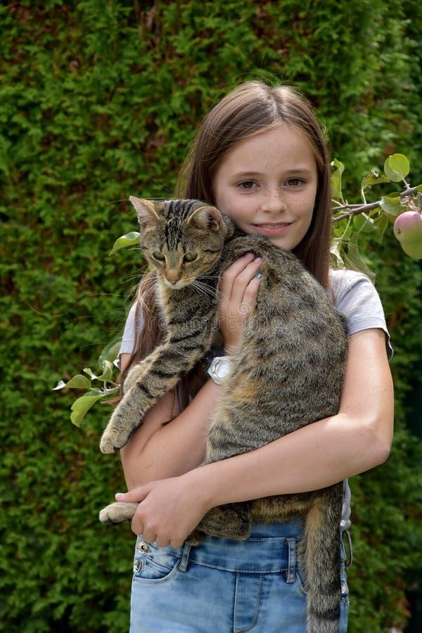 Flickan bär katten arkivfoton