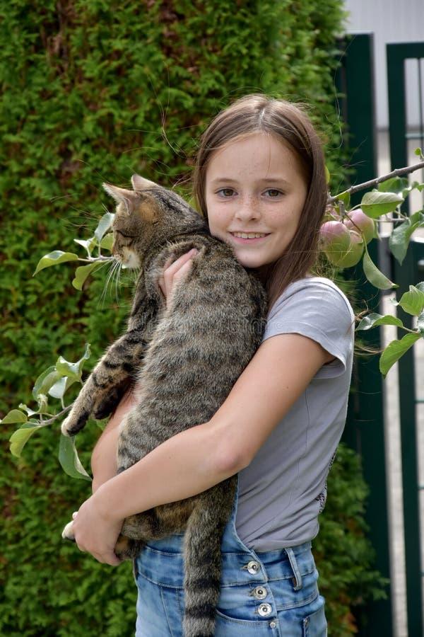 Flickan bär katten royaltyfria bilder