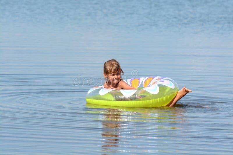 Flickan badar i havet med en cirkel royaltyfri fotografi