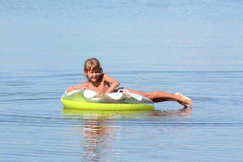 Flickan badar i havet med en cirkel royaltyfria foton