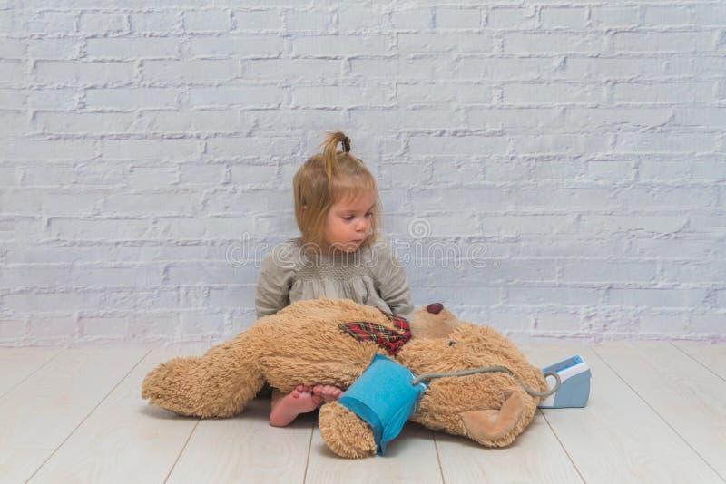 Flickan barn mäter trycket av leksakbjörnen, lekdoktor arkivbilder