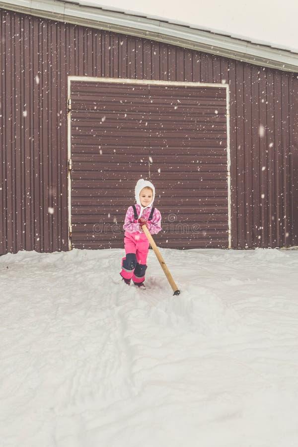 Flickan behandla som ett barn den stora skyffeln tar bort snö från banan i trädgården på garaget royaltyfri foto