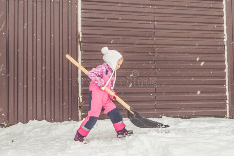 Flickan behandla som ett barn den stora skyffeln tar bort snö från banan i trädgården på garaget royaltyfria foton
