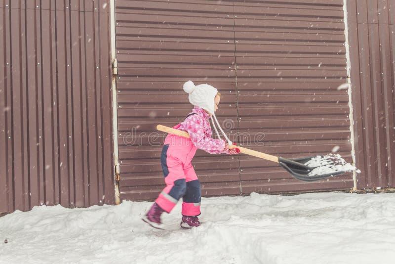 Flickan behandla som ett barn den stora skyffeln tar bort snö från banan i trädgården på garaget arkivfoto