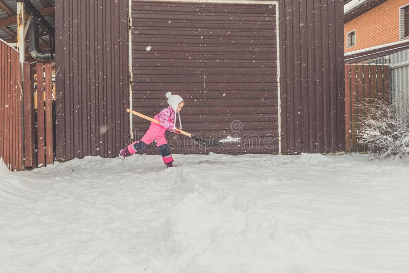 Flickan behandla som ett barn den stora skyffeln tar bort snö från banan i trädgården på garaget arkivbilder