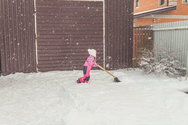 Flickan behandla som ett barn den stora skyffeln tar bort snö från banan i trädgården på garaget royaltyfri bild