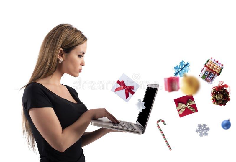 Flickan beställer jul som gåvor i ett online- shoppar royaltyfri foto
