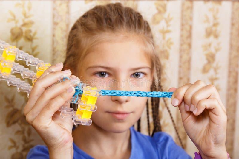 Flickan betraktar ett hemlagat armband arkivfoto