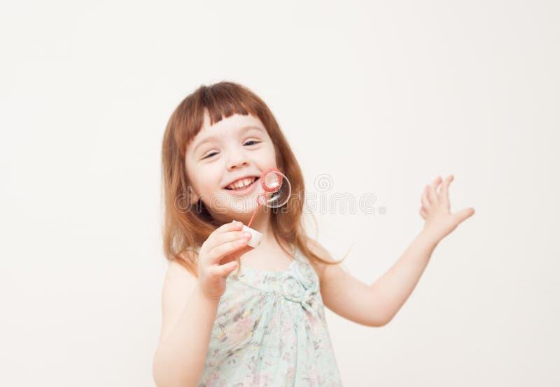Flickan blåser såpbubblor på monophonic bakgrund royaltyfri bild