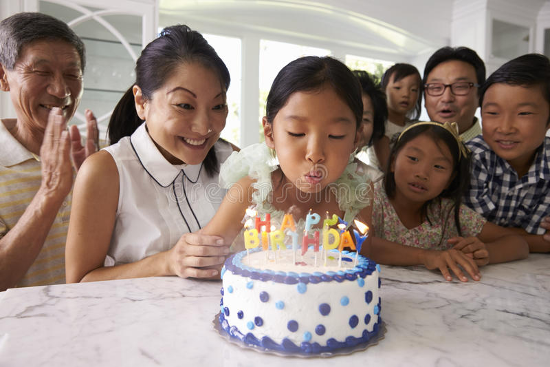 Flickan blåser ut stearinljus på familjfödelsedagberöm royaltyfri fotografi