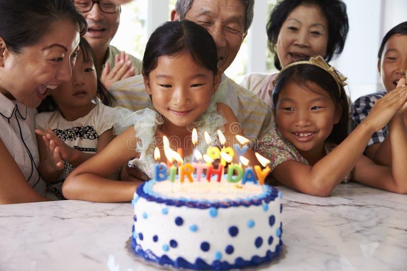 Flickan blåser ut stearinljus på familjfödelsedagberöm arkivbilder