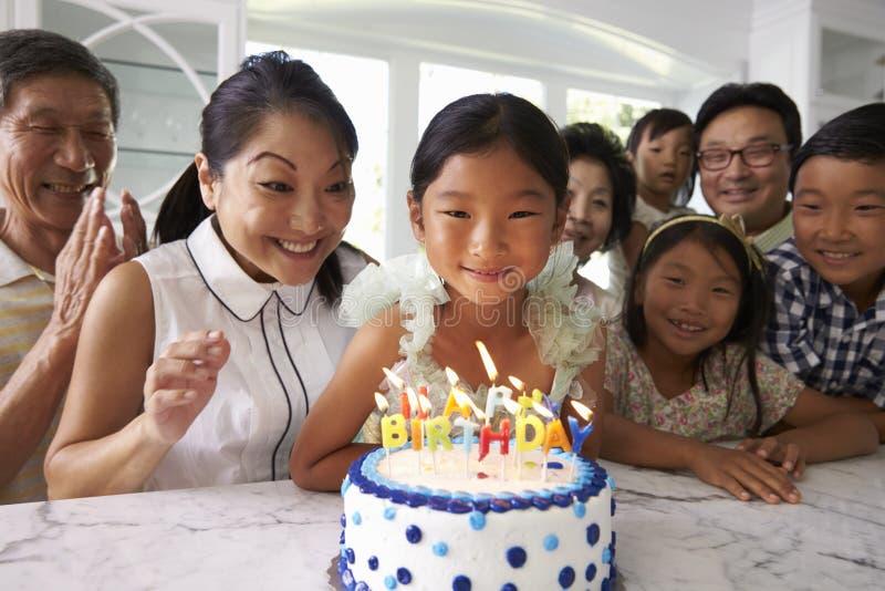 Flickan blåser ut stearinljus på familjfödelsedagberöm royaltyfria bilder