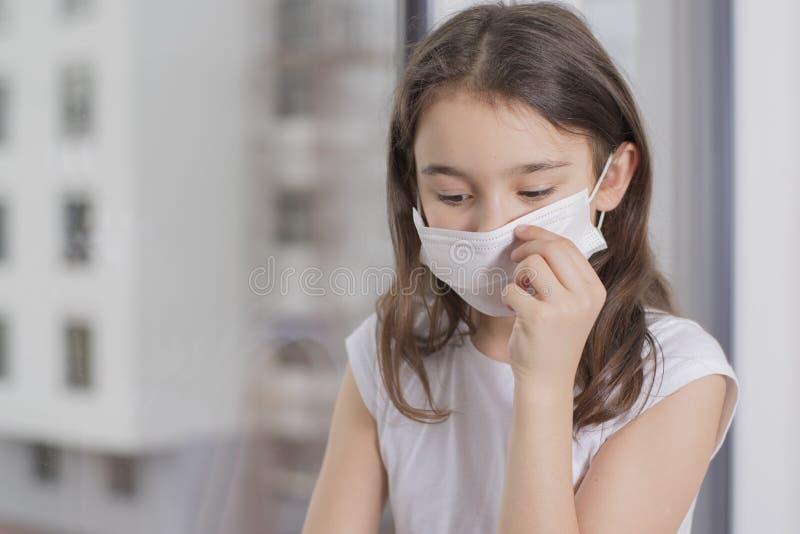 Flickan blev sjuk och kan inte gå ut symtom från Wuhan coronavirus och epidemiologiskt virus En liten flicka med mask för skydd a royaltyfri bild