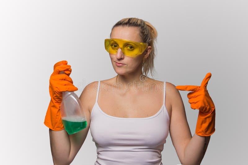 Flickan blondinen i handskar med hjälpmedel för tvättande fönster royaltyfri bild