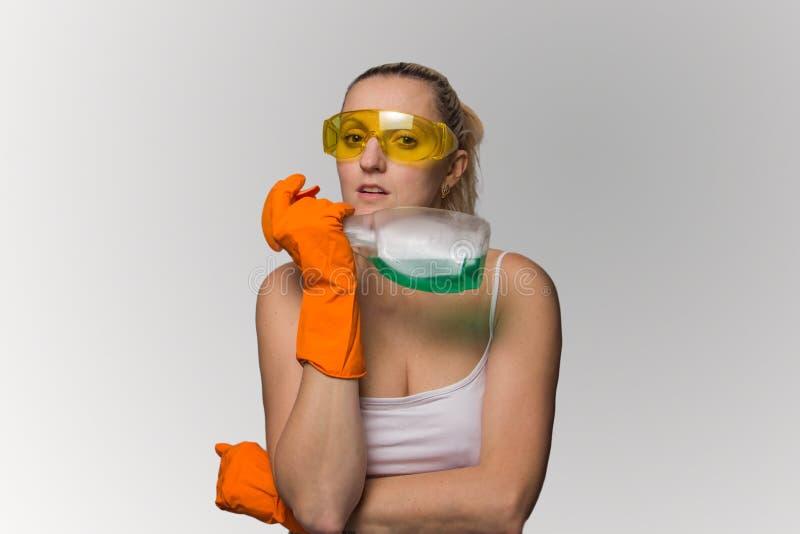 Flickan blondinen i handskar med hjälpmedel för tvättande fönster royaltyfri fotografi