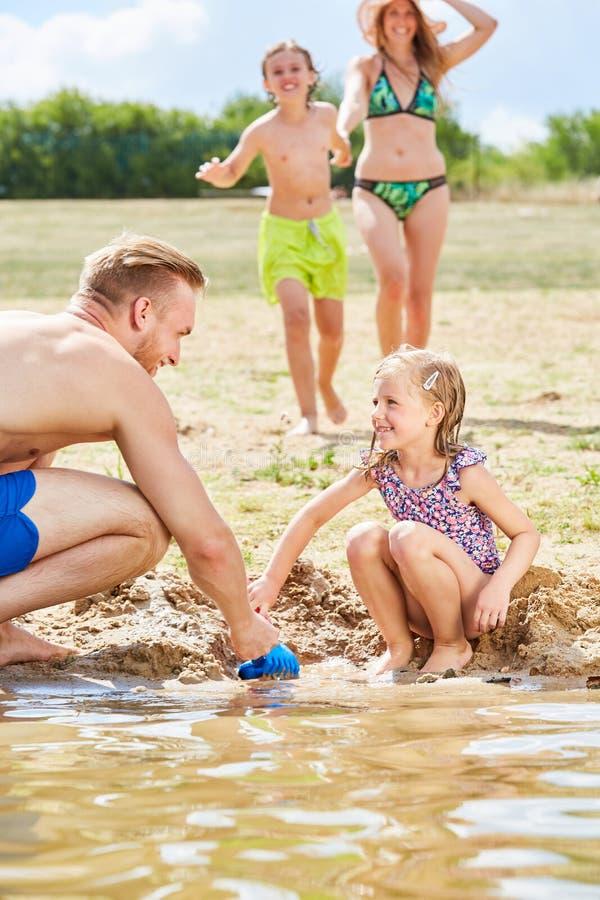 Flickan bygger en sandslott med hennes fader arkivbild