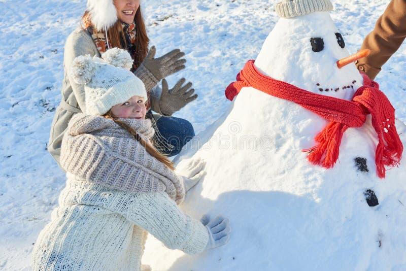 Flickan bygger snögubben i vinter fotografering för bildbyråer