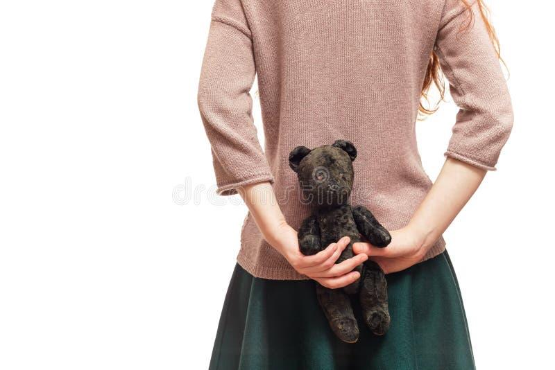 Flickan döljer den gamla björnen bak henne tillbaka arkivfoton