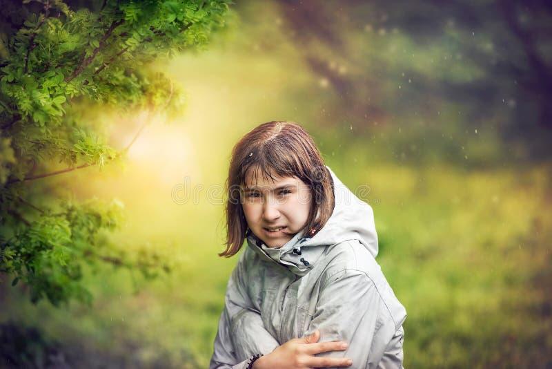 flickan döljer från regnet under trädet Kvinna i trädgården royaltyfria bilder