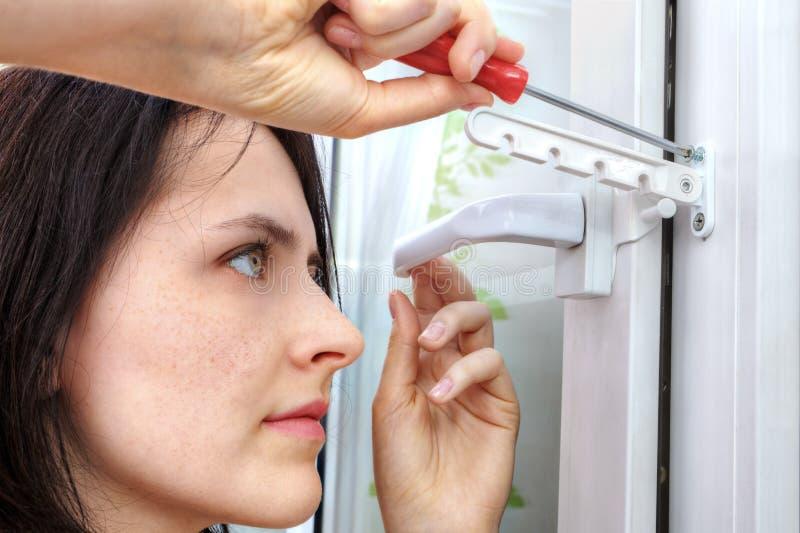 Flickan drar åt skruven som säkrar limiteren av öppningsplast-fönstret arkivbilder